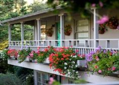 Dolores Street, Carmel CA.  Love the flower boxes at floor level on 2nd floor porch and hanging baskets on the wall.