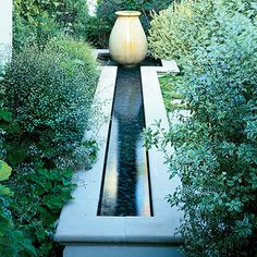 Urn of Stone - Water spills from an antique French stone urn into a rectangular pool and a narrow, 18-inch-deep channel in this San Clemente, California garden. A pump recirculates the water. The designis the focal point of a garden corner that invites quiet contemplation. Scented geraniums and other foliage plants grow nearby.