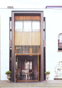 Tom loves using industrial roll-up (ie, garage) doors, this is an interesting cross between that and a bamboo screen.