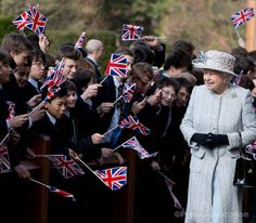 Queen Elizabeth II is greeted by pupils waving the union flag at Reed's School, in Cobham, Thursday 6 March 2014