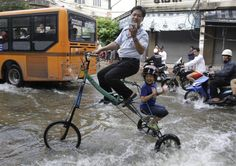 A Thai man takes pictures with his son on a bicycle which he custom built to go through floodwaters in Bangkok, Thailand. (AP)