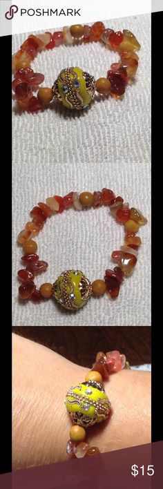 Fire Agate Gemstone Stretch Bracelet Fire agate has a bold and beautiful color. It looks very striking paired with the bright yellow Indonesian bead and the golden marble. Beautiful warm colors and all natural stones! PeaceFrog Jewelry Bracelets