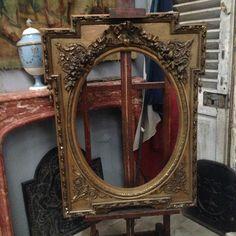 miroir ovale dans un encadrement rectangulaire dorure apparente . XX siècle .