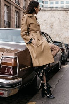 Fashion blogger Beatrice Gutu in 70's vintage car editorial wearing neutral leather coat with fishnet tights and lace up boots