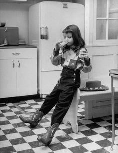 A young girl wearing a cowgirl outfit while drinking milk and eating a sandwich in her kitchen. Photograph by Nina Leen. USA, 1948.