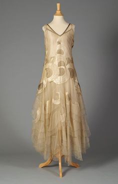 Evening dress of cream tulle with circular designs in silk and gold thread, American, late 1920s. Via Kent State University Museum.