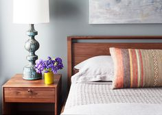 Gray bedroom with chic striped pillow,  purple flowers on wood bedside table and blue table lamp