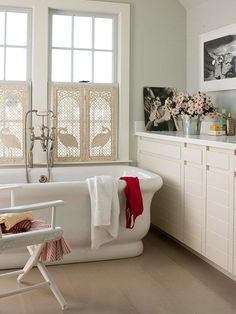 Vintage Serenity-This relaxing bathroom atmosphere keeps its cool with neutral walls and furnishings. Vintage cream-color window shutters add character to the subdued walls. Black-and-white artwork provides a hint of contrast while staying true to the room's vintage feel
