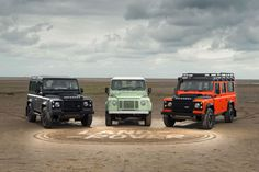 A black, mint green and orange Land Rover Defender parked on a beach