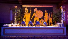 A mural of mythical warriors and goddesses formed the backdrop for the main buffet in the ballroom, which was covered...