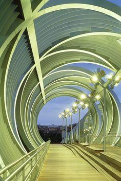 Ponte Pedonal Arganzuela, em Madri, Espanha. A passarela permite que as pessoas atravessem de um lado do Parque Manzanares para o outro, de um lado do rio para o outro. Também proporciona acesso direto ao parque abaixo. À noite é possível fazer um passeio luminoso. Arquitetura: Dominique Perrault Arquitetura. Fotografia: Georges Fessy / DPA / ADAGP.