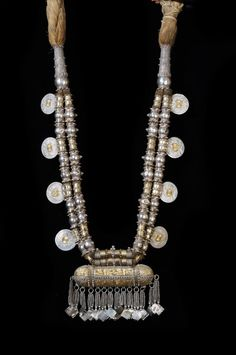 """Coins featured are so-called Maria Theresa thalers.  The coin was widely used for trade in the Middle East. This is a very, very good quality Omani necklace. Made in the early to mid 20th c, with a silver content of 85%, and real gold also used. The tube-like box at the bottom is a """"Koran holder"""" (often called """"hirz"""") which was due to hold verses from the Koran to protect the wearer. The piece is in perfect condition. Shown in Truus Daalder, *Ethnic Jewellery and Adornment*, p. 386."""