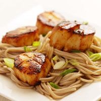 Miso-Glazed Scallops with Soba Noodles  From: EatingWell  This Japanese-inspired dish uses one sauce--a sweet/salt combination of mirin and miso--to make both the marinade for the scallops and the caramelized pan sauce for the noodles. A good pairing would be a simple green salad dressed with a citrus vinaigrette.