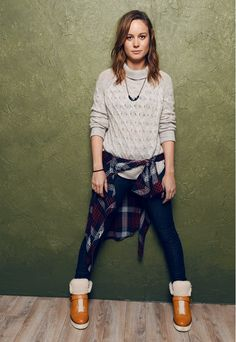 Brie Larson looking cozy in a chunky knit sweater, Rails flannel button-down, and Coach boots
