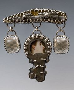 """Lip Lock  2010    2""""  (pin)  sterling and fine silver, steel slag, key, postcard fragment, mica, candywrapper, handmade lace, lingerie netting, crystal by Kristin Diener"""