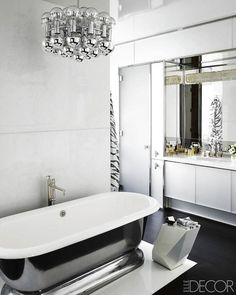 Modern bathroom features modern, polished chrome light pendant over freestanding bathtub paired with floor-mounted tub filler against marble partition atop marble floor.