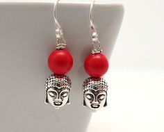 SKU: SE_200   These Buddha head earrings feature bright red cinnabar beads with antiqued silver buddha charms (two-sided design) suspended