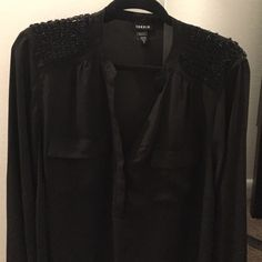 Torrid blouse Black torrid blouse with sequins detail size 2. Blouse runs a bit large. Some of the sequins are missing in the right shoulder. Please look at the third and fourth pictures. torrid Tops Blouses