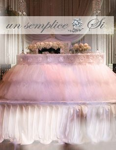 From our Si Collection Romantic and elegant this Tulle and Beaded Lace with Satin rose embellished table cloth will create an atmosphere that is timeless and classic. The skirting and table cap are sewn together for easy setup. ( Also available in 2 separate pieces , ask us for customized design ) LED lighting can be added under for added glamour. Made with 4 fully gathered tulle layers and a gathered organza layer to add body. Each tablecloth has a beaded lace cap to cover the full top of…