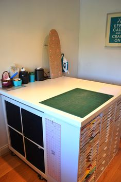 CRAFTY STORAGE.  mini ironing board.  ruler hung from hook on side of cabinet.