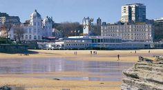 Playa de El Sardinero, con la ciudad de Santander al fondo -   . Su tradición marinera y comercial se une a una vocación turística centenaria, que tiene en la célebre playa de El Sardinero, en el paseo Marítimo y en la península de La Magdalena sus mayores atractivos.