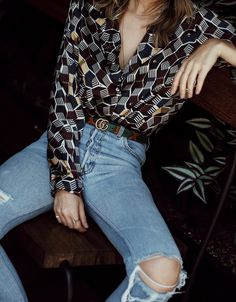 Printed silk button-down blouse, Gucci belt, and distressed, high-rise jeans.