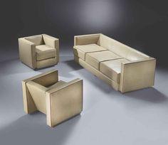 Boris Lacroix (1902-1984)  Mobilier de salon, vers 1930  Comprenant un canapé trois places et deux fauteuils cubiques, entièrement re-gainés de cuir beige gansé rouge, les dossiers inclinés, reposant sur deux pieds latéraux cylindriques en aluminium, le canapé muni d'un troisième pied Le canapé : Hauteur : 66 cm. (26 in.) ; Longueur : 229 cm. (90 1/8 in.) ; Profondeur : 84 cm. (33 1/8 in.) Chaque fauteuil : Hauteur : 64,5 cm. (25 3/8 in.) ; Largeur : 75 cm. (29½ in.) ; Profondeur : 80 cm…
