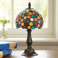 """For desk, dresser or bedside, our handmade art glass lamp is a lighthearted take on the Tiffany tradition. The domed shade glows atop an art Nouveau style bronze finished base. 60w max. 6-1/2"""" DIA. x 13""""H."""