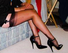 Black dress upskirt to show black suspenders with black nylon stockings and black high heels.