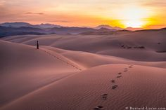 I took this photo of the sun rising over spectacular dunes in Northern Namibia. The black mountains beyond are in Angola.