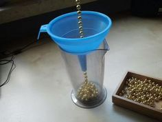 Various lengths of matching bead chains. Slide with pincer grasp the chain pieces through the funnel into the measuring cup. Slow release required at end of chain. If the chain is not kept straight, getting the beads through the narrow opening is impossible. The different lengths of chain pieces have different requirements. The longer the chain, the more difficult it becomes. This game requires concentration and a steady hand.  Add a ruler as an extension to match chain lengths.