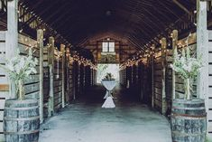 globe lights and cocktail tables line the long aisle at the large polo barn at saxony farm