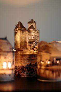 """Plaatjes van """"oude"""" gebouwen uitknippen en rond een glas of glazen pot plakken. Waxinelichtje erin en klaar. Zo kun je een hele stad bouwen."""