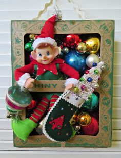Here is a fun Christmas decoration made with vintage and new materials!This whimsical over-the-top decoration features a vintage Christmas Shiny Brite ornament box with a silly elf hold. Vintage Christmas Crafts, Homemade Christmas Decorations, Christmas Crafts For Gifts, Retro Christmas, Christmas Love, Christmas Projects, Christmas Holidays, Christmas Vignette, Christmas Barbie