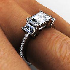 Platinum three stone saddle set diamond emerald cut engagement ring with side flanking emerald cut side diamonds and small round diamond side shank accents.