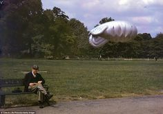 Stiff upper lip: A man determined to keep a sense of normality reads a book on a park bench as a moored barrage balloon, designed to scupper air attacks, floats in the background and a second, right, soars above