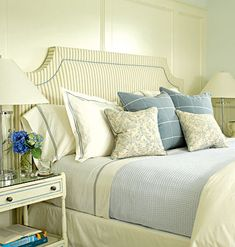 Guest bedroom in Southampton, NY with creamy white walls, an upholstered blue-and-white striped headboard, and light blue bed linens