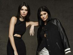 Kendall Jenner, wearing a black cutout dress, and Kylie Jenner, wearing a letterman jacket, model their Topshop Christmas Collection.