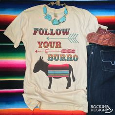 Follow Your Burro design with arrows and serape blanket on the adorable little donkey. Printed on a soft junior or unisex fit cream shirt. The junior fittted tee runs a size small and the unisex will fit like a regular t-shirt.  100% combed cotton jersey  Junior measurements across chest: S 16.5 M 17 L 18 XL 19.5 XXL 21  Unisex measurements across:  S 18 across M 20 across L 21 across XL 23 across XXL 24.5 across  ©️️ Rockin A Design 2015. All rights reserved.
