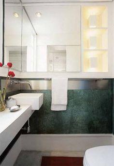 O cimento queimado tingido criou um tapete vermelho e cobriu de verde as paredes deste lavabo. Para amenizar o contraste de tons, branco na bancada e nos armários. Projeto de Alice Martins e Flávio Butti.