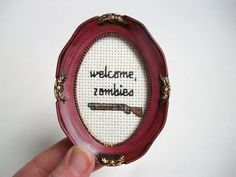 Welcome Zombies (with shotgun) mini completed cross stitch in frame or hoop (pictured in examples of secondhand frames, dark copper square frame, natural wood embroidery hoop, and rectangular black frame)  ---The Story---  Heres a small, inexpensive cross stitch gift for housewarming, birthdays, or any occasion, for anyone who digs zombies. (Metaphorically.) Its an expansion on the brains sweet brains mini stitch I made as a housewarming gift for a friend, now a part of zombie and…