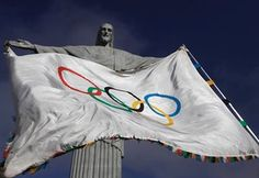 The Olympic Flag flies in front of Christ the Redeemer statue in Rio de Janeiro