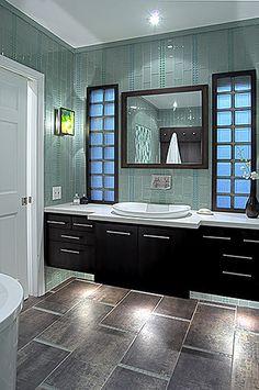 Green Glass Tiled wall, light countertop/sink, dark vanity, under vanity lit, medium dark tiled floor.