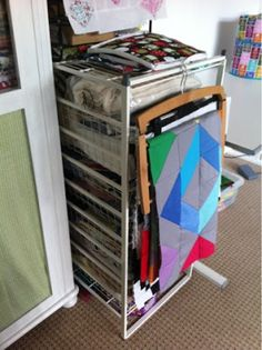 """The """"Quilty Creations"""" blogger's Sewing Room Reveal -- I like how she hides storage by hanging some WIPs on it."""