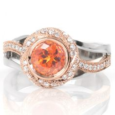 Design 3227 is a Knox Jewelers custom engagement created in Minneapolis, Minnesota. Inspired from our Motion setting, this version includes an center orange sapphire enclosed within a spiraling diamond halo, finished in a two-tone look.