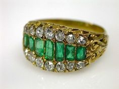 One 18 karat yellow gold ring. Seven emerald cut emeralds (0.89 carats). Twenty-eight old European cut diamonds (1.43 arats: SI clairty: F-G colour).    $5500