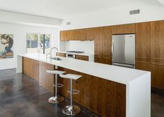 Modern kitchen remodel. Ribbon mahogany cabinetry, Staron countertops with a waterfall edge, breakfast bar, stainless steel appliances and an island that runs the length of the kitchen. Mid Century ranch home for sale in Arcadia. Phoenix / Scottsdale Arizona