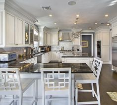 huge kitchen with white cabinets and black counters libbysellsdenver