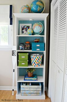 Kids room beadboard backed bookcase - love the styling with the globes and map decoupage crate.