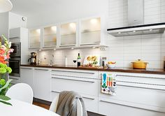White small kitchen on one wall with long long drawer and cabinet pulls in brushed nickel. Frosted glass upper cabinets show just enough. One Wall Kitchen, Kitchen Wall Cabinets, Long Kitchen, Kitchen Nook, Upper Cabinets, Kitchen Flooring, Kitchen Backsplash, New Kitchen, Kitchen Ideas